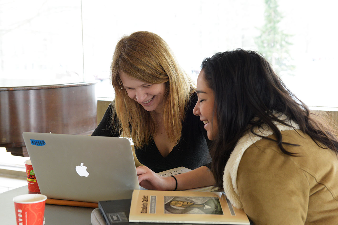 Two women looking at a laptop, smiling. ©Wikimedia